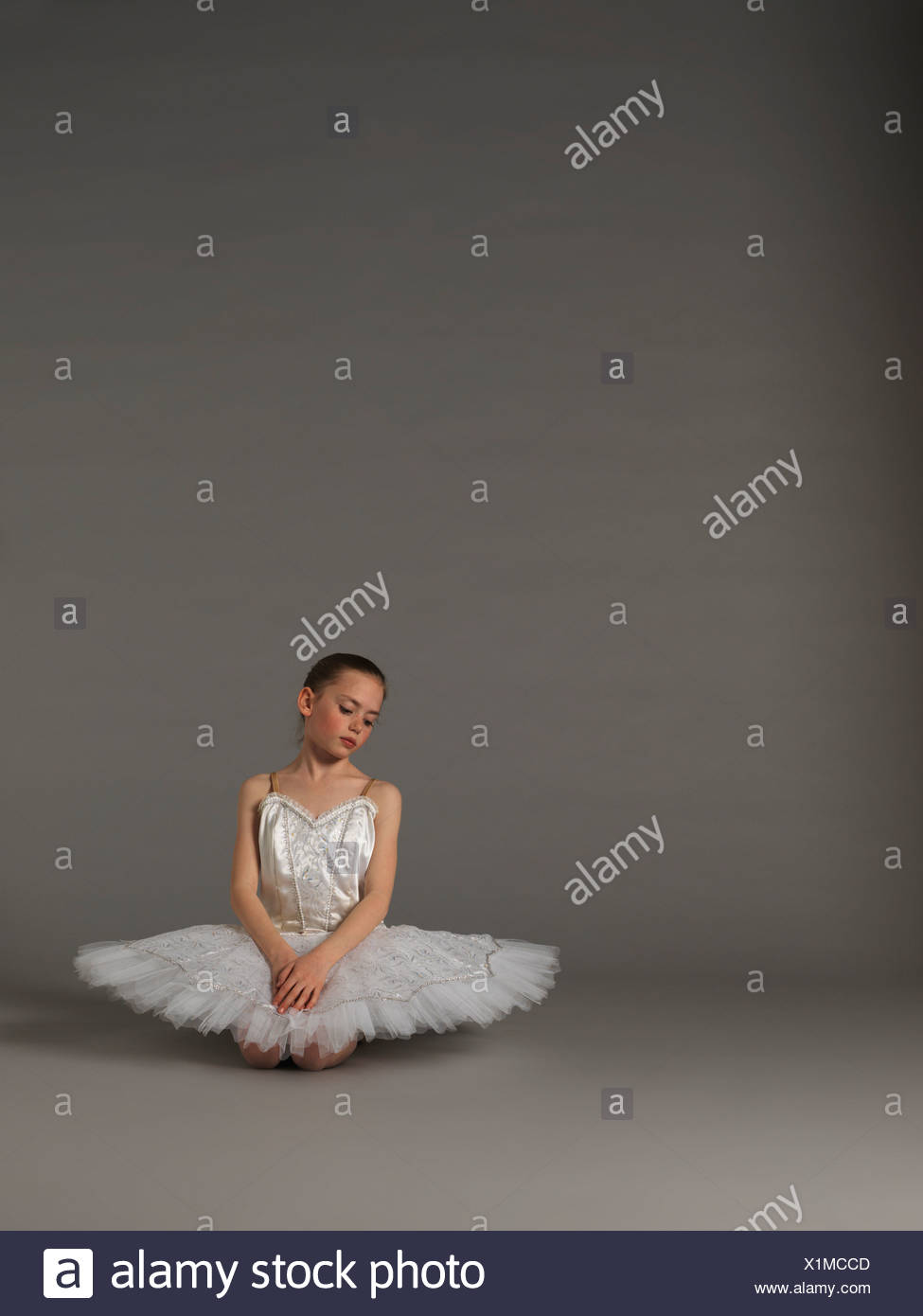 Girl in white tutu kneeling. - Stock Image