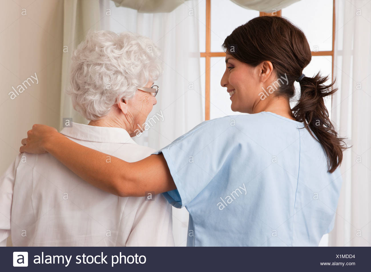 USA, Illinois, Metamora, Rear view of female nurse consoling senior woman - Stock Image