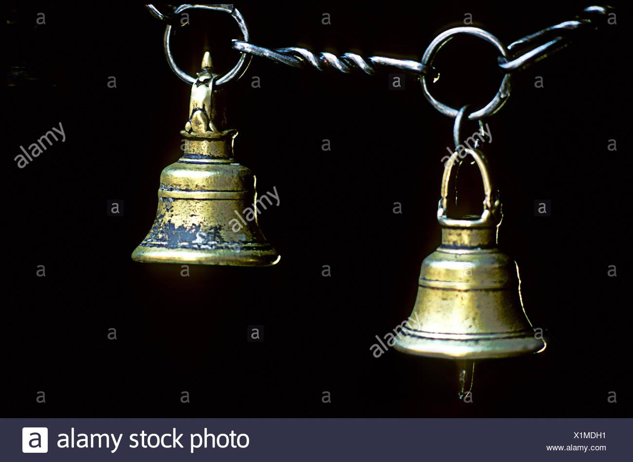 Brass bells hang in a Katmandu temple. - Stock Image