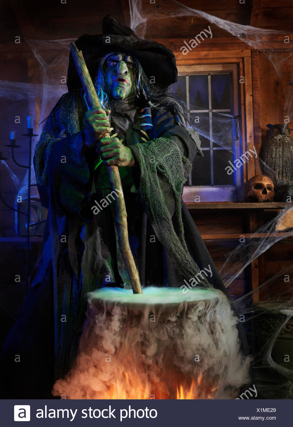 Scary old witch stirring potion in a cauldron inside her cabin on Halloween - Stock Image