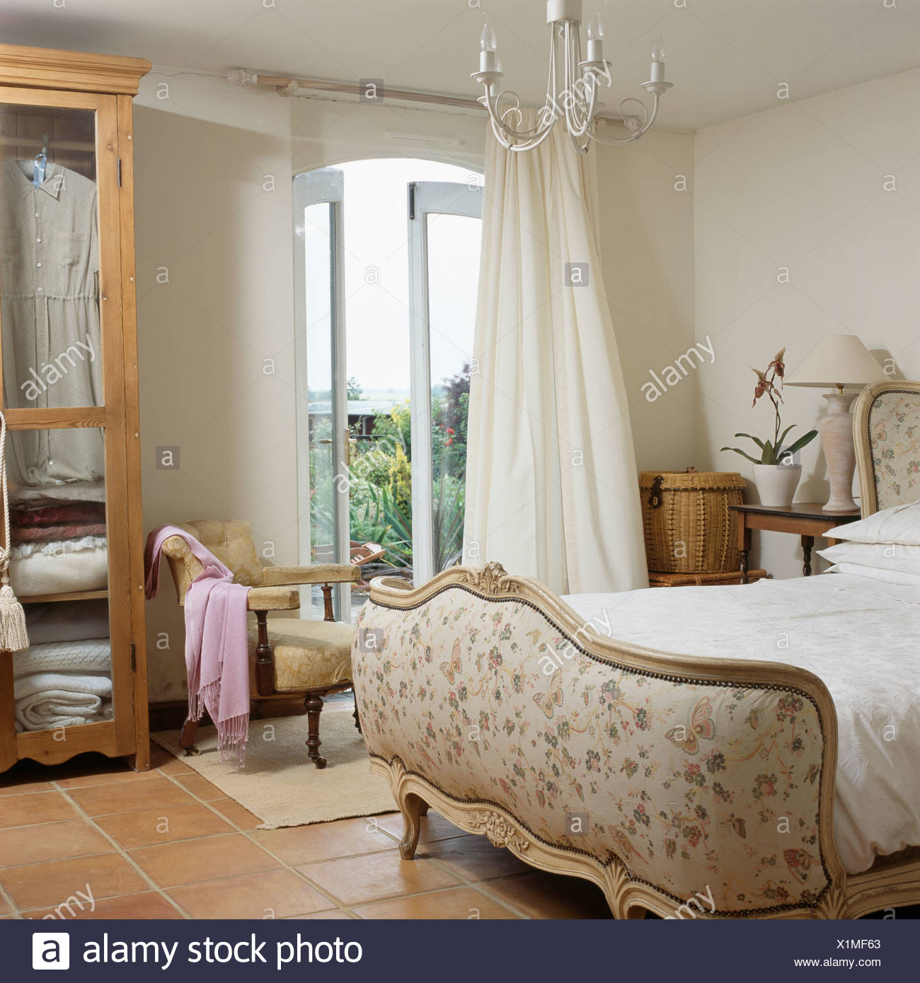 Upholstered French Bed In Cream Country Bedroom With Cream Curtains At  French Windows With View Of The Garden