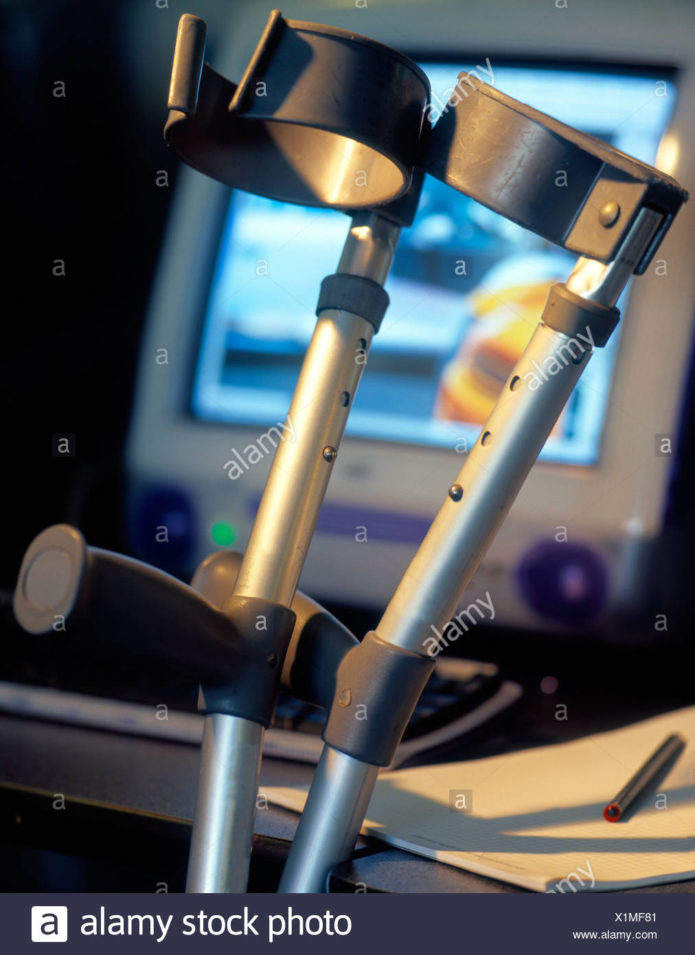 Close-up of crutches leaning against computer table - Stock Image