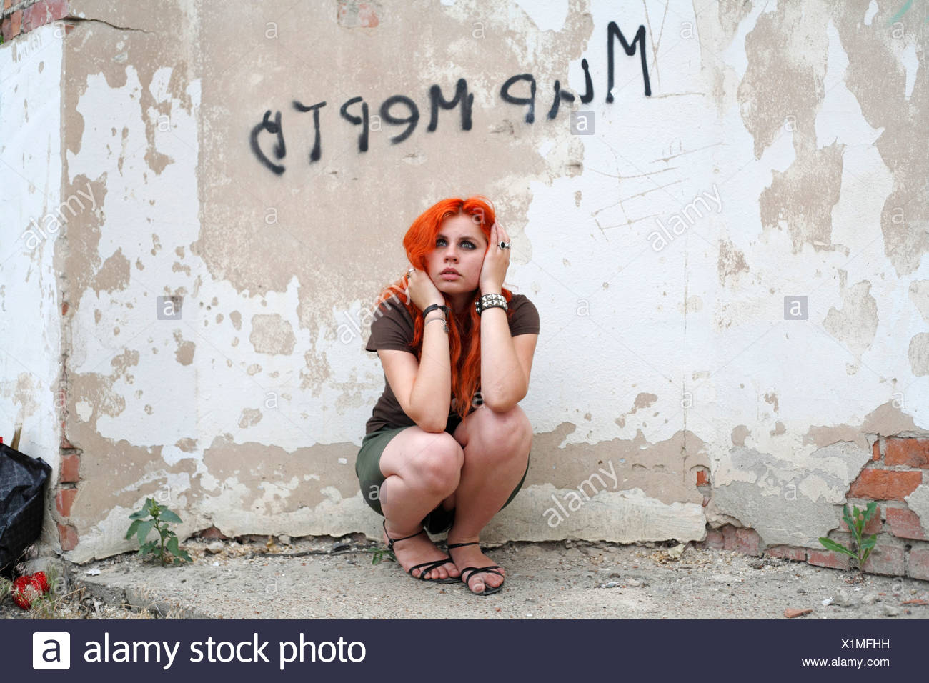 pretty redhead girl against obsolete wall - Stock Image