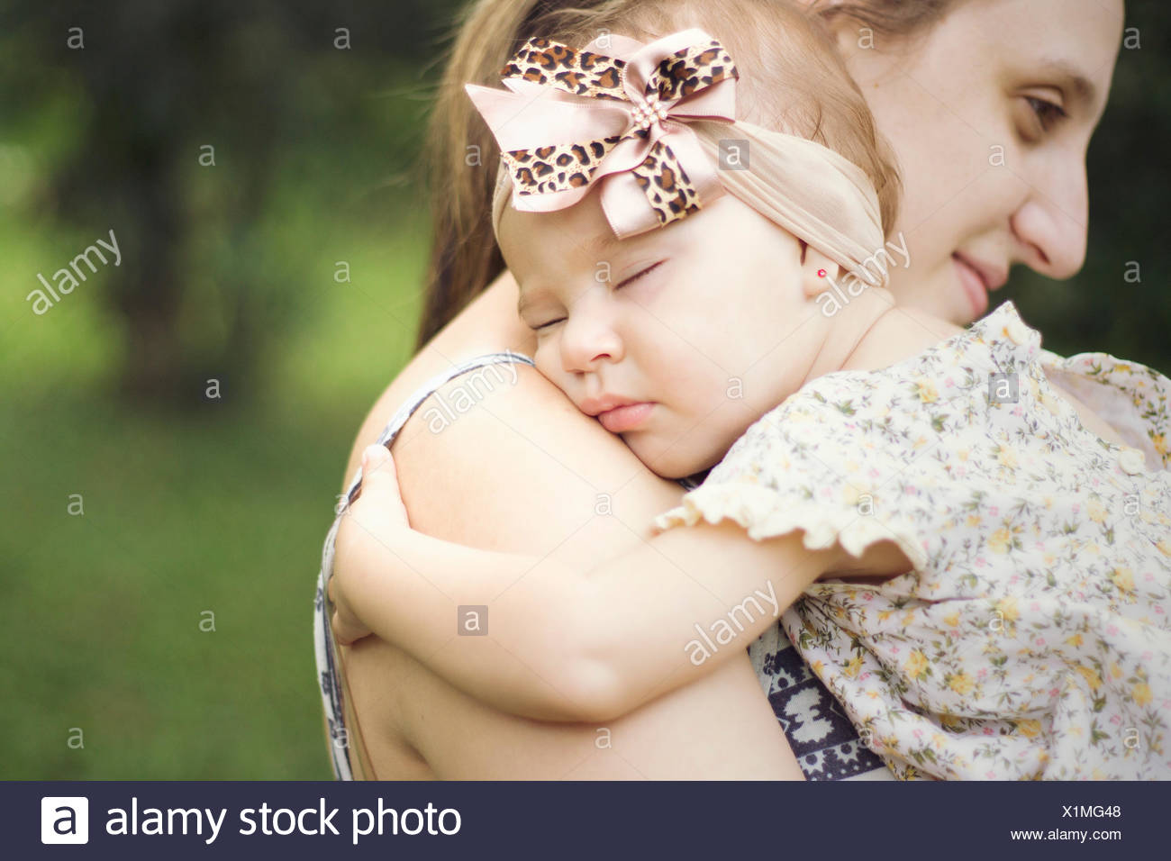 Close-Up Side View Of A Mother Carrying Baby Outdoors - Stock Image