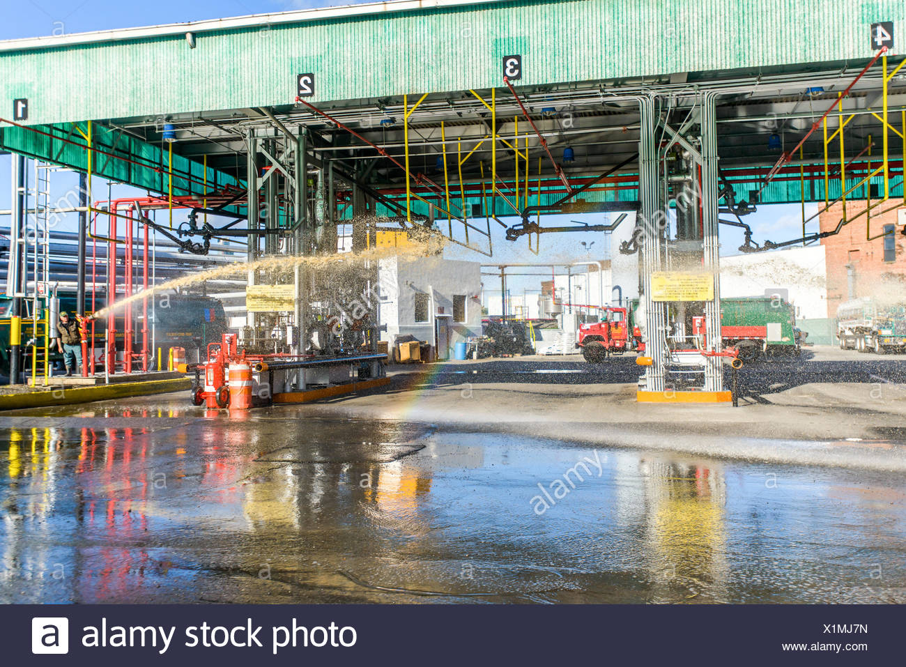 Worker pressure hosing biofuel oil tanker cleaning station at biofuel plant - Stock Image