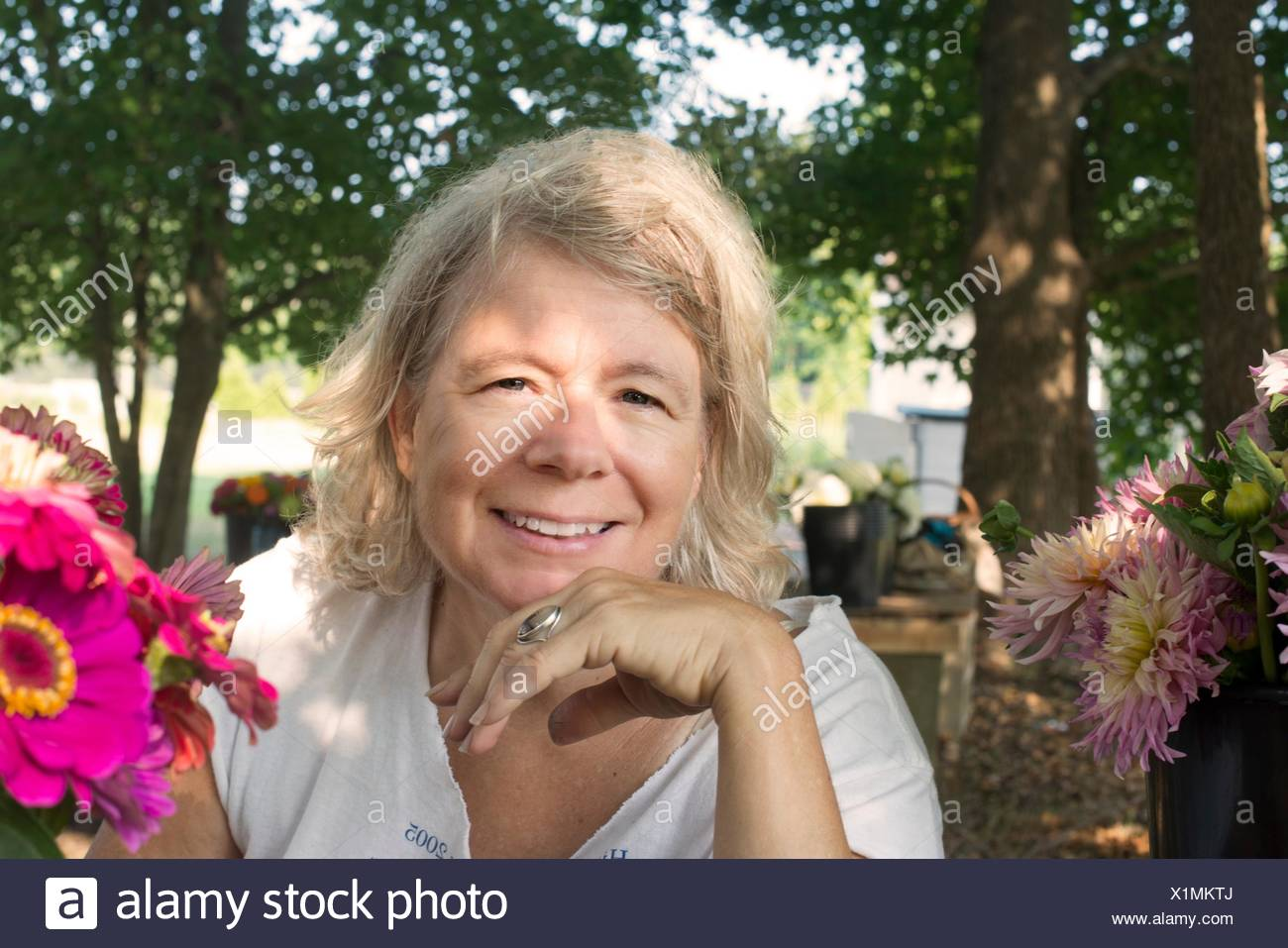 Portrait of senior female farmer with cut flowers - Stock Image