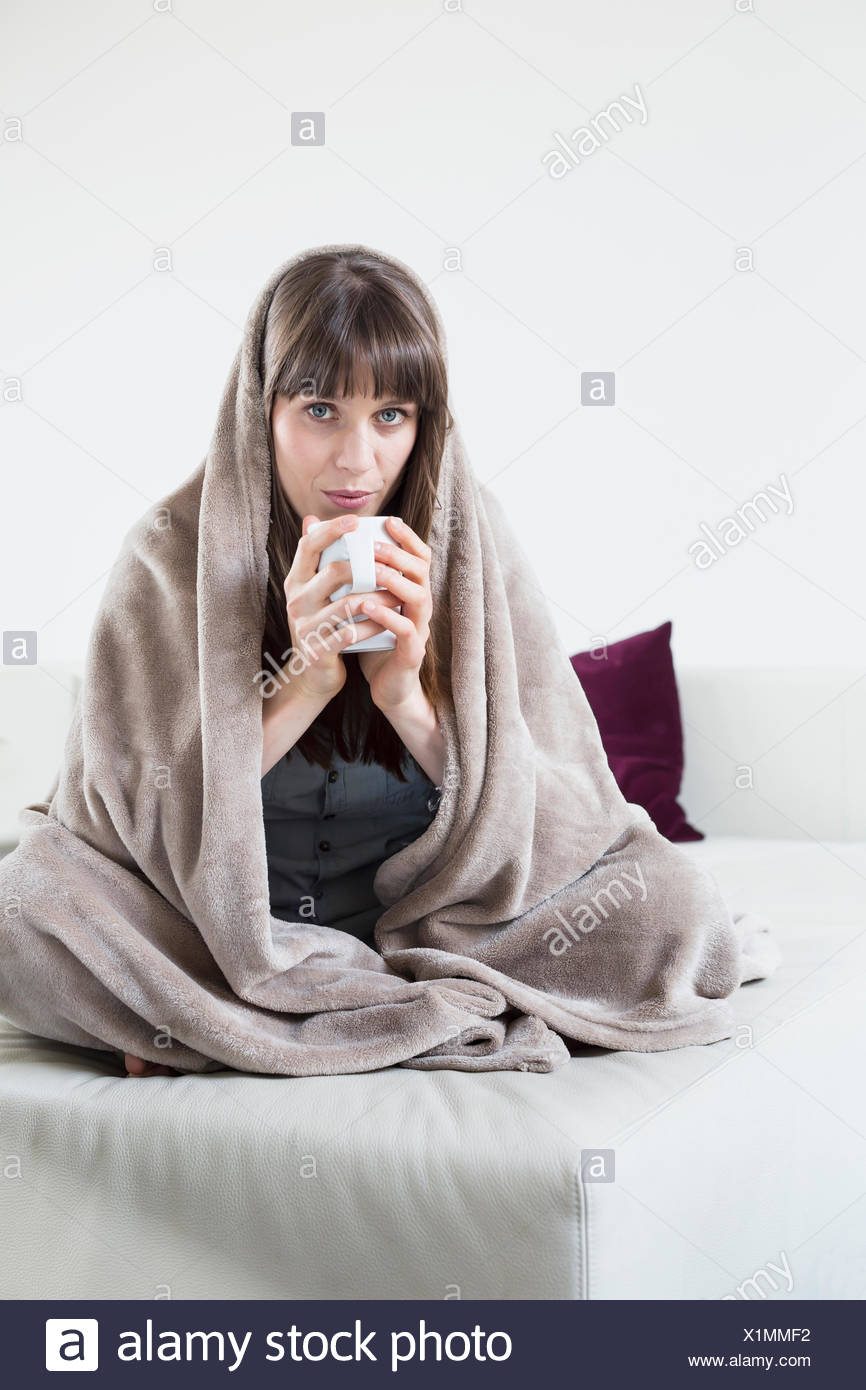 Portrait of mid adult woman covered with blanket and holding cup of tea - Stock Image