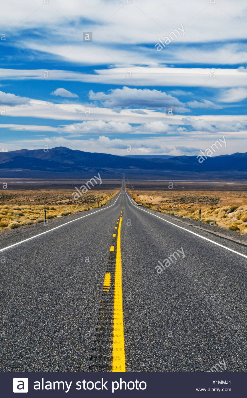 Highway 50, The Loneliest Road in America, disappears into the distance in the Nevada desert. - Stock Image