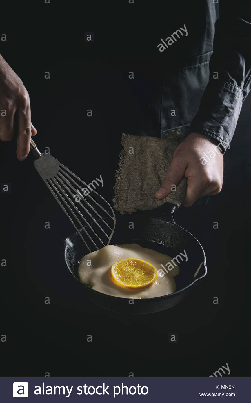 Man chef in black apron cooking pancakes with orange in cast-iron pan. Turns the pancake. Dark rustic style. Toned image - Stock Image