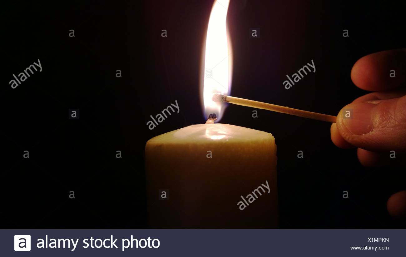 Match lighting candle in dark - Stock Image