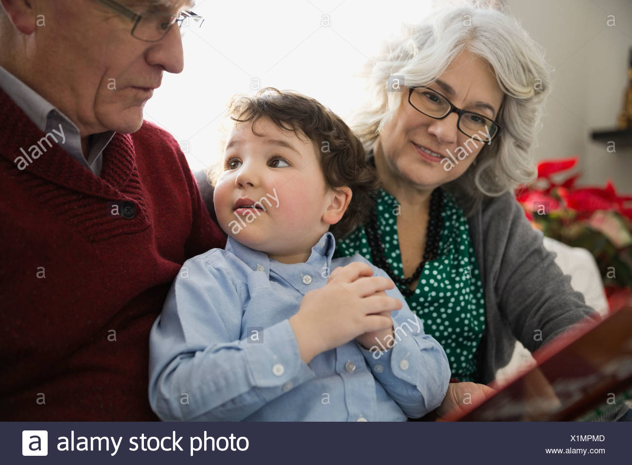 Grandson with grandparents at home during Christmas - Stock Image