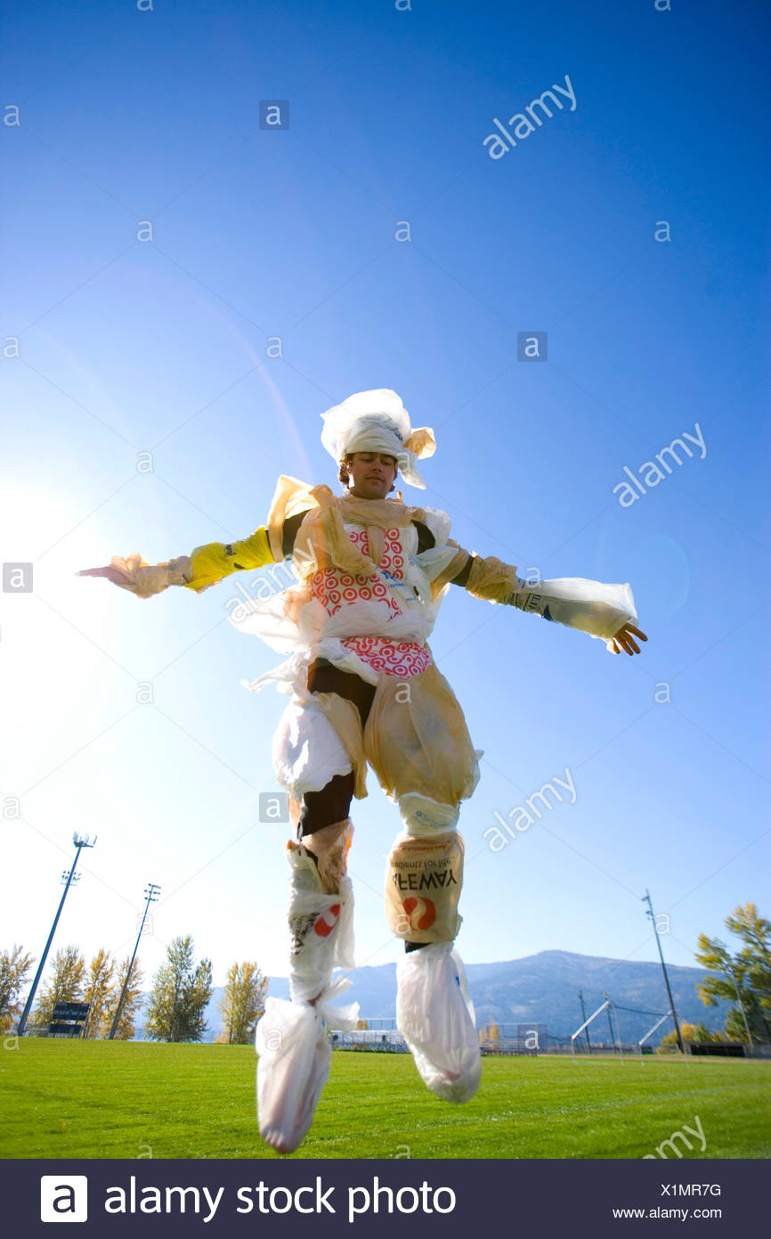 Portrait of adult man dressed in plastic bags jumping in the air - Stock Image