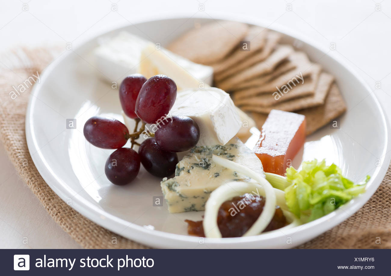 Cheese plate with a selection of cheese and biscuits. - Stock Image