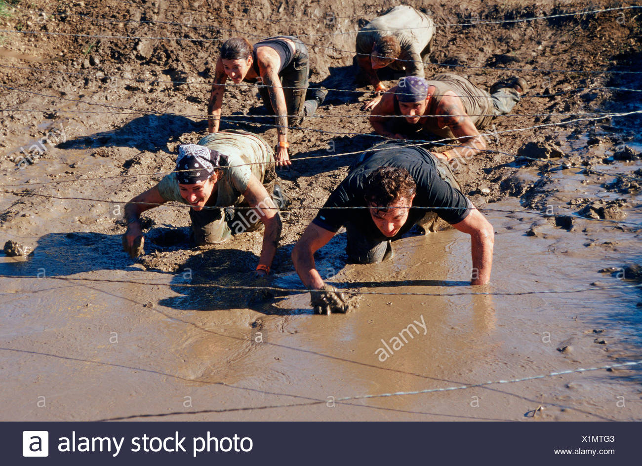 Group of people army crawling on their bellies under steel wires through the mud - Stock Image