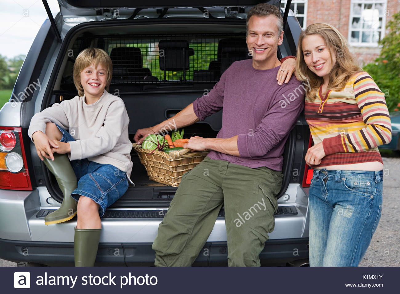 Two generation family posing beside car boot with basket of vegetables smiling portrait - Stock Image