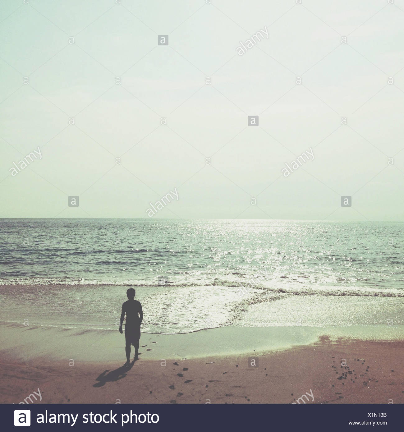Silhouetted figure on beach walking away from sea - Stock Image