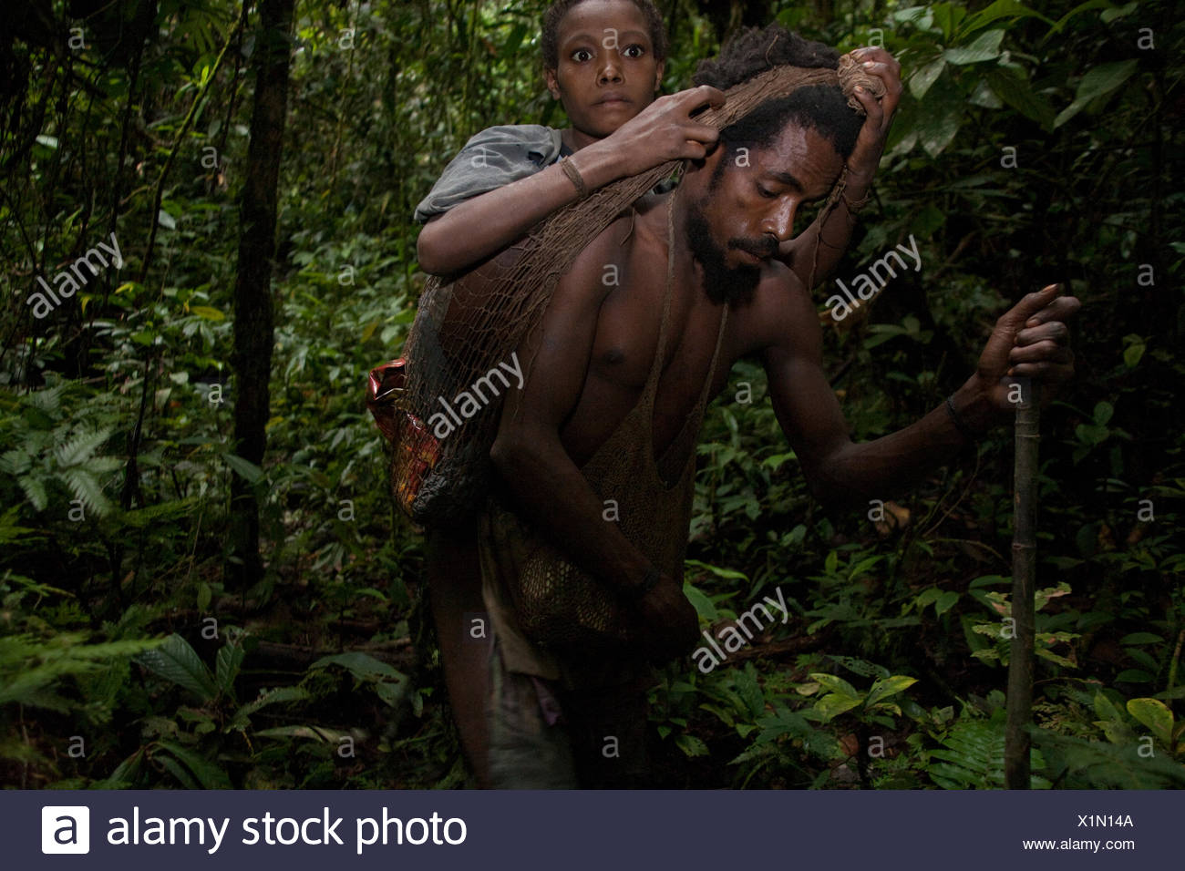 A husband carries his pneumonia-stricken wife on the two-day trek to the nearest health clinic. - Stock Image