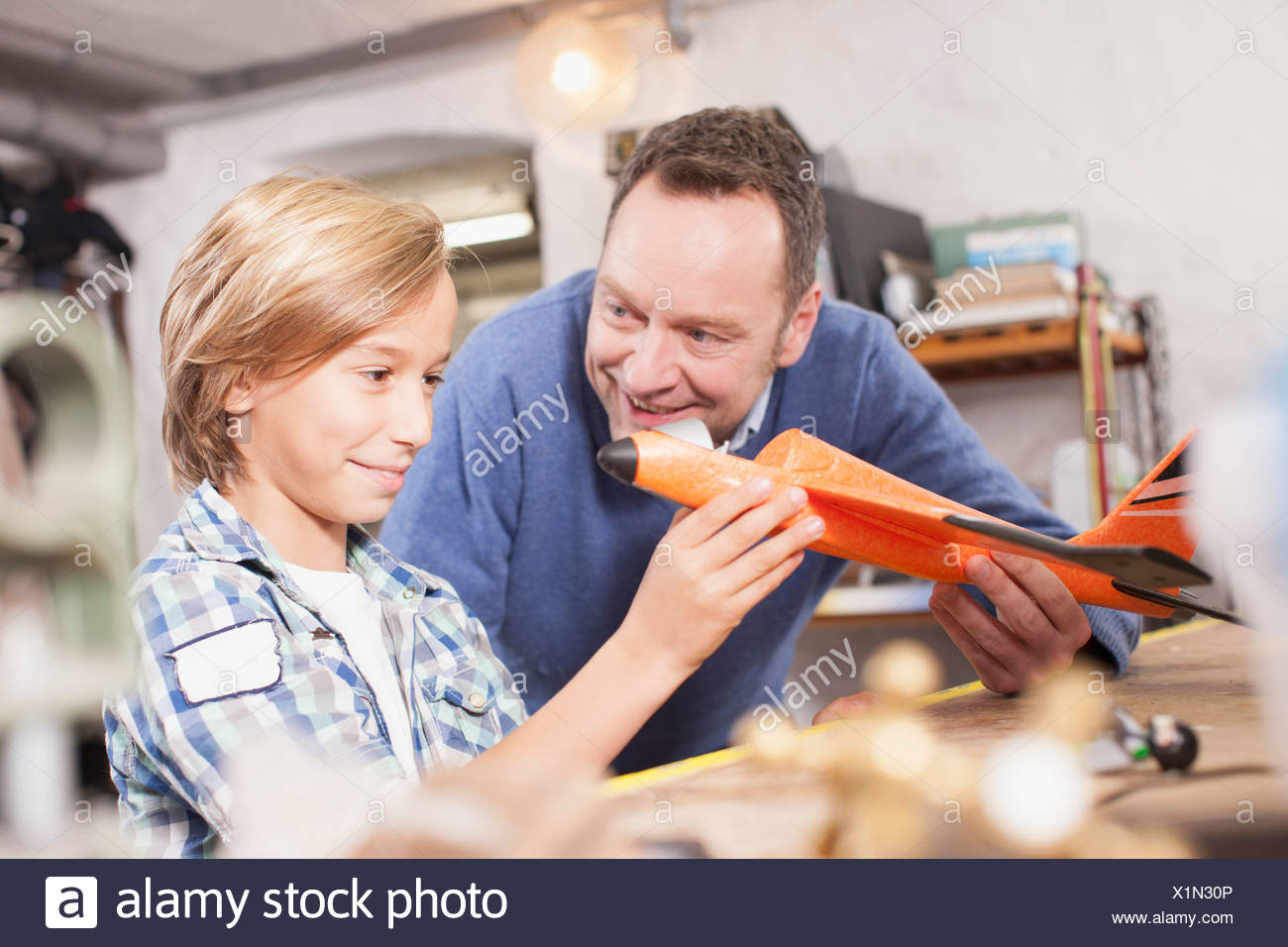 Germany, Leipzig, Father and son repairing aircraft - Stock Image
