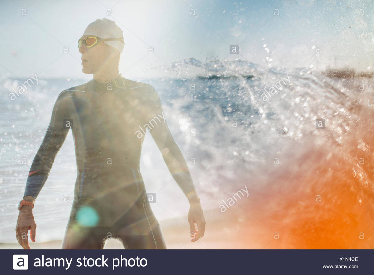 A swimmer in a wet suit standing by the water's edge. - Stock Image