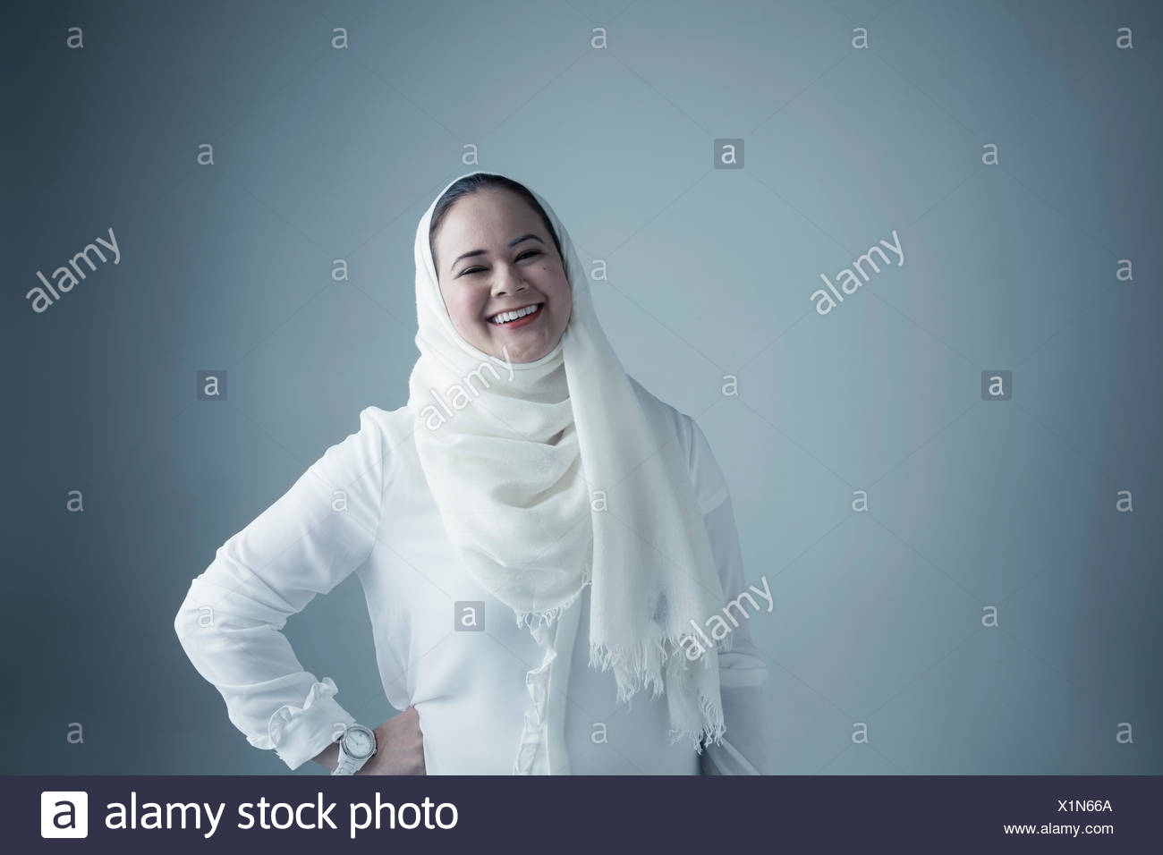 Portrait Middle Eastern young woman in white hijab and burka laughing - Stock Image