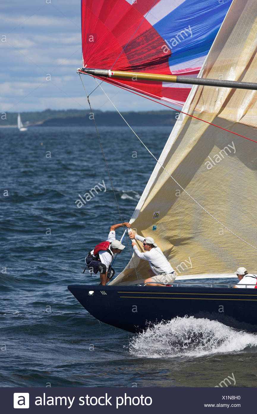 The crew on 'Freedom' take down the head sail after the spinnaker is flying while racing in the 12 Metre World's Competition 200 - Stock Image