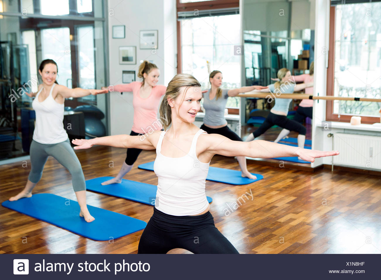 Group of women doing Pilates exercises arms outstretched - Stock Image