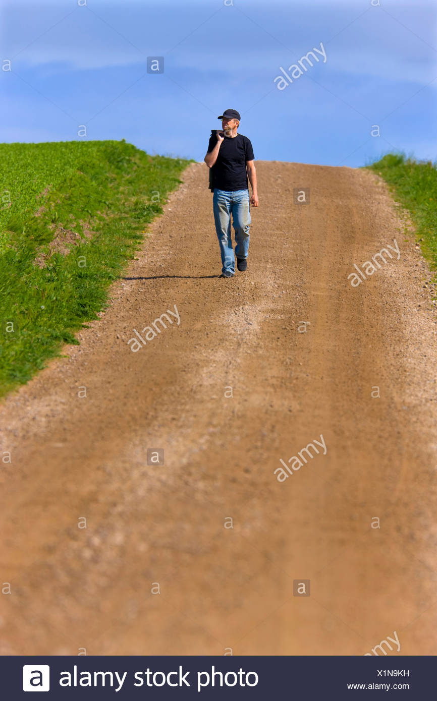 Man in casuals walking on the dirt country road along landscape - Stock Image