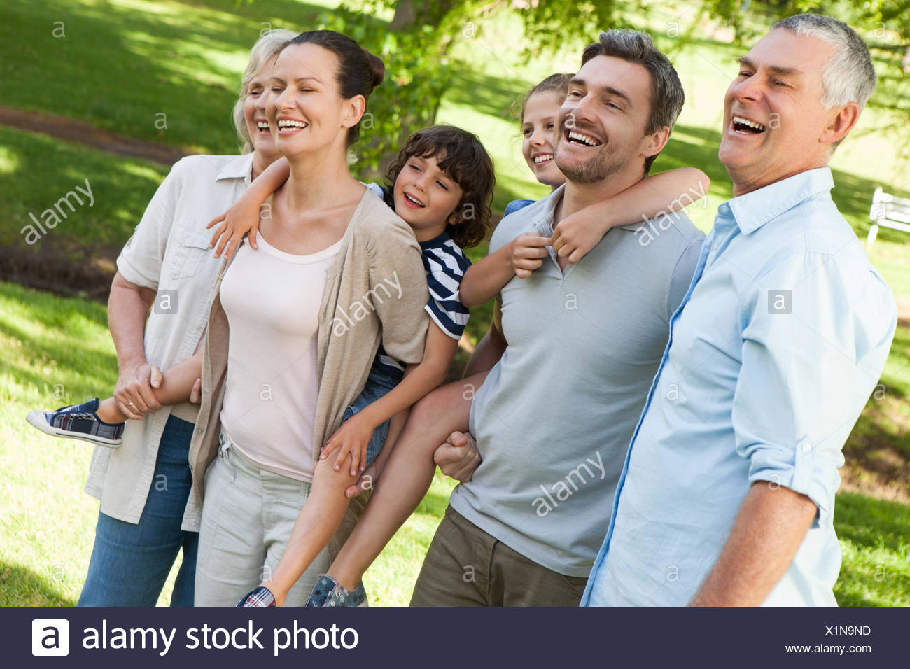 Cheerful extended family standing at park - Stock Image