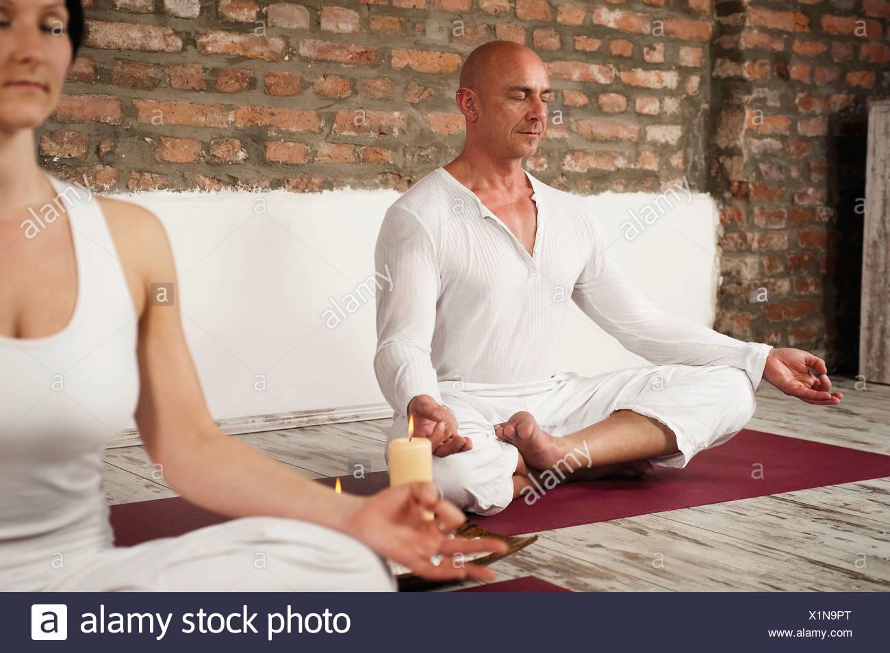 Couple Practising Yoga, Lotus Pose - Stock Image