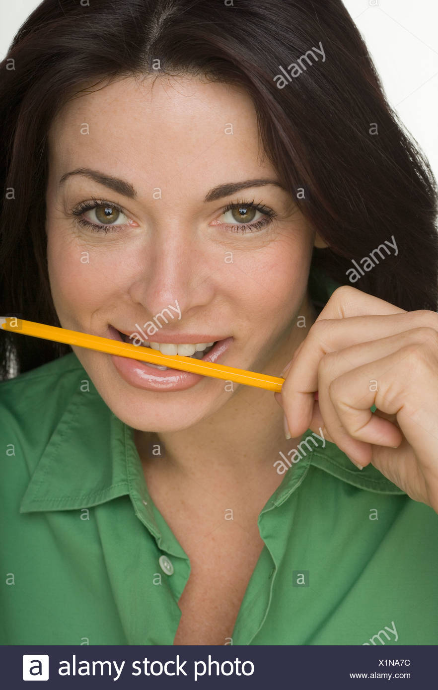 Portrait of woman with yellow pencil between teeth - Stock Image