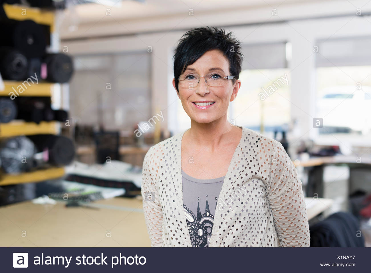 Portrait of mature seamstress in workshop - Stock Image