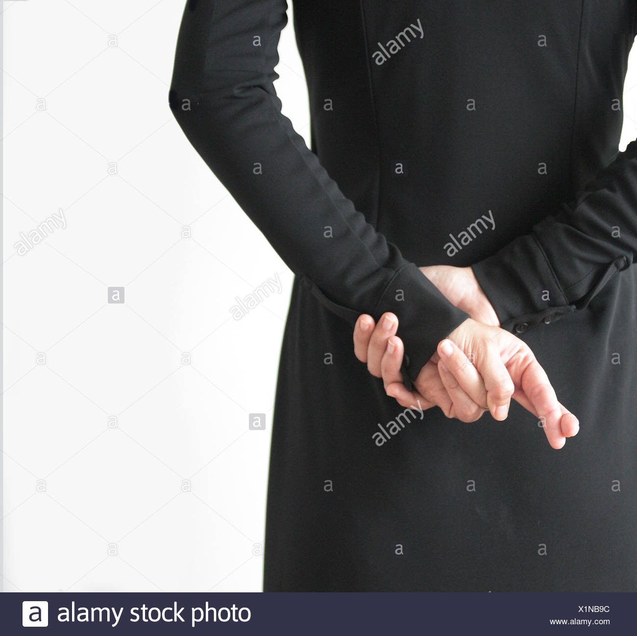 Rear view of a woman with fingers crossed behind back - Stock Image