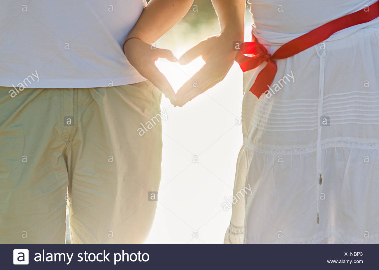 Hands of two people making the shape of heart - Stock Image