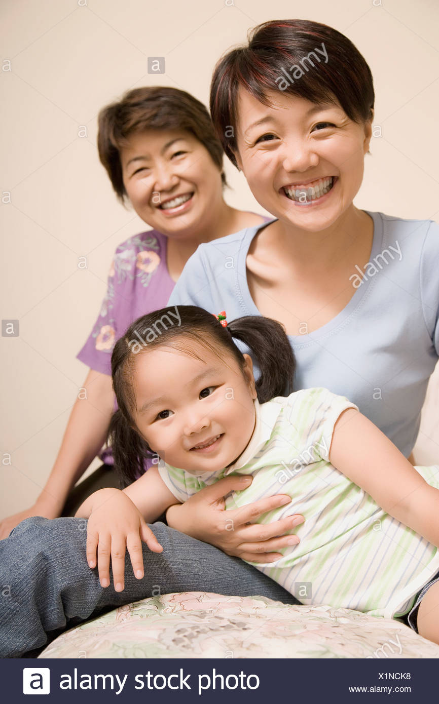 Portrait of a mature woman smiling with her daughter and granddaughter - Stock Image