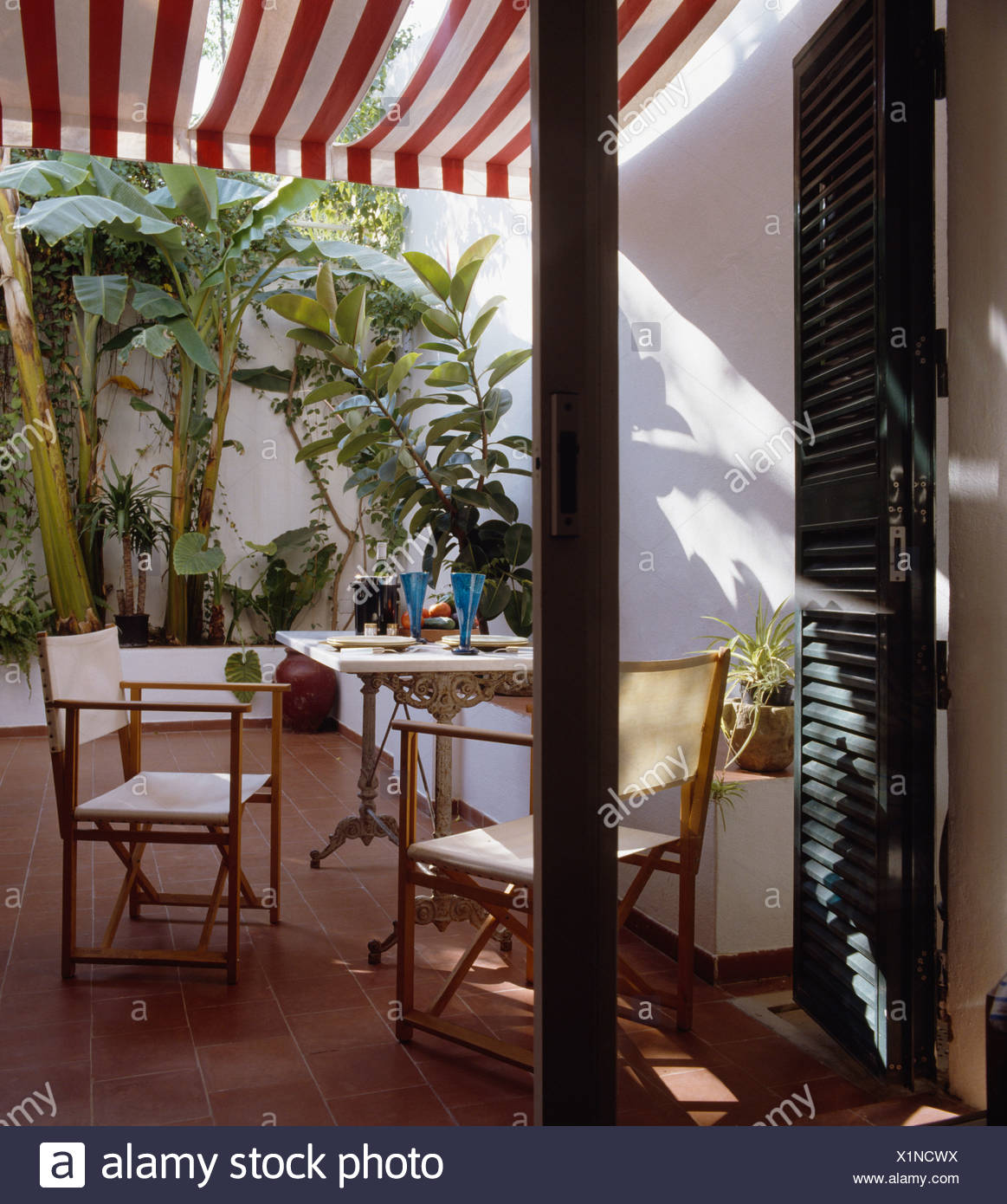 White Directors Chairs And Metal Table In Small Terracotta Tiled Inner Courtyard With Striped Awning