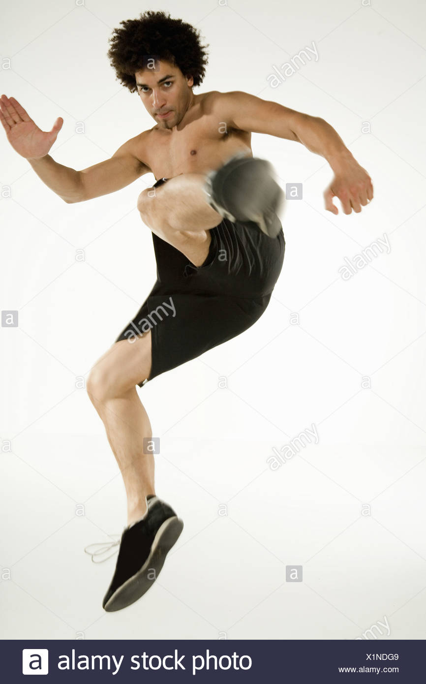 Bare-chested man jumping and kicking Stock Photo