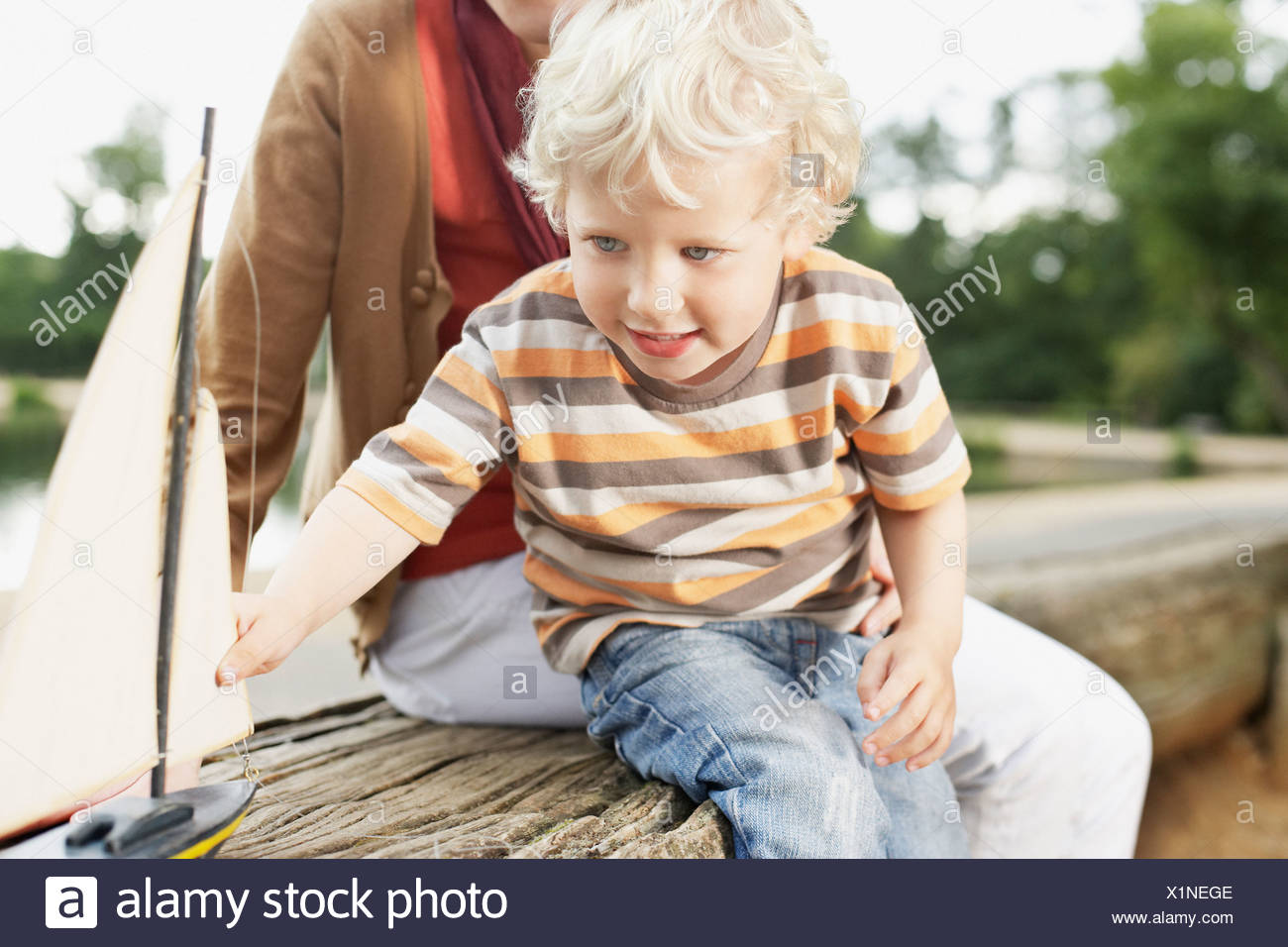 Boy playing with toy sailboat - Stock Image
