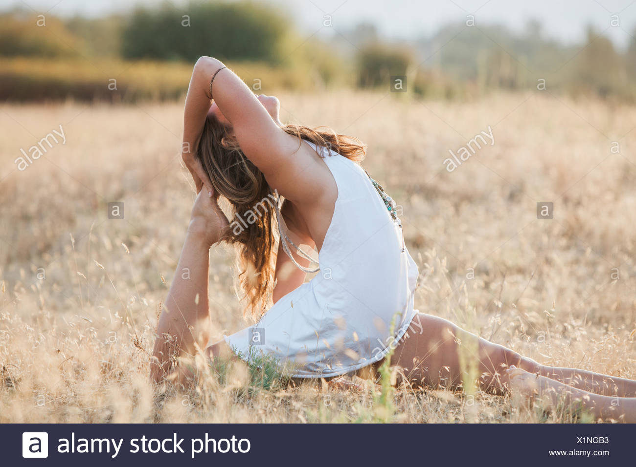 Boho woman in royal king pigeon pose in sunny rural field - Stock Image