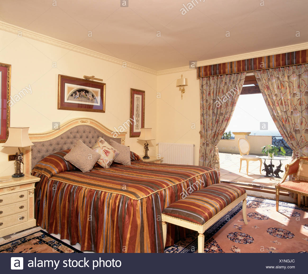 Bed With Multi Colored Striped Bedlinen In Spanish Apartment Bedroom With  Floral Curtains On Patio