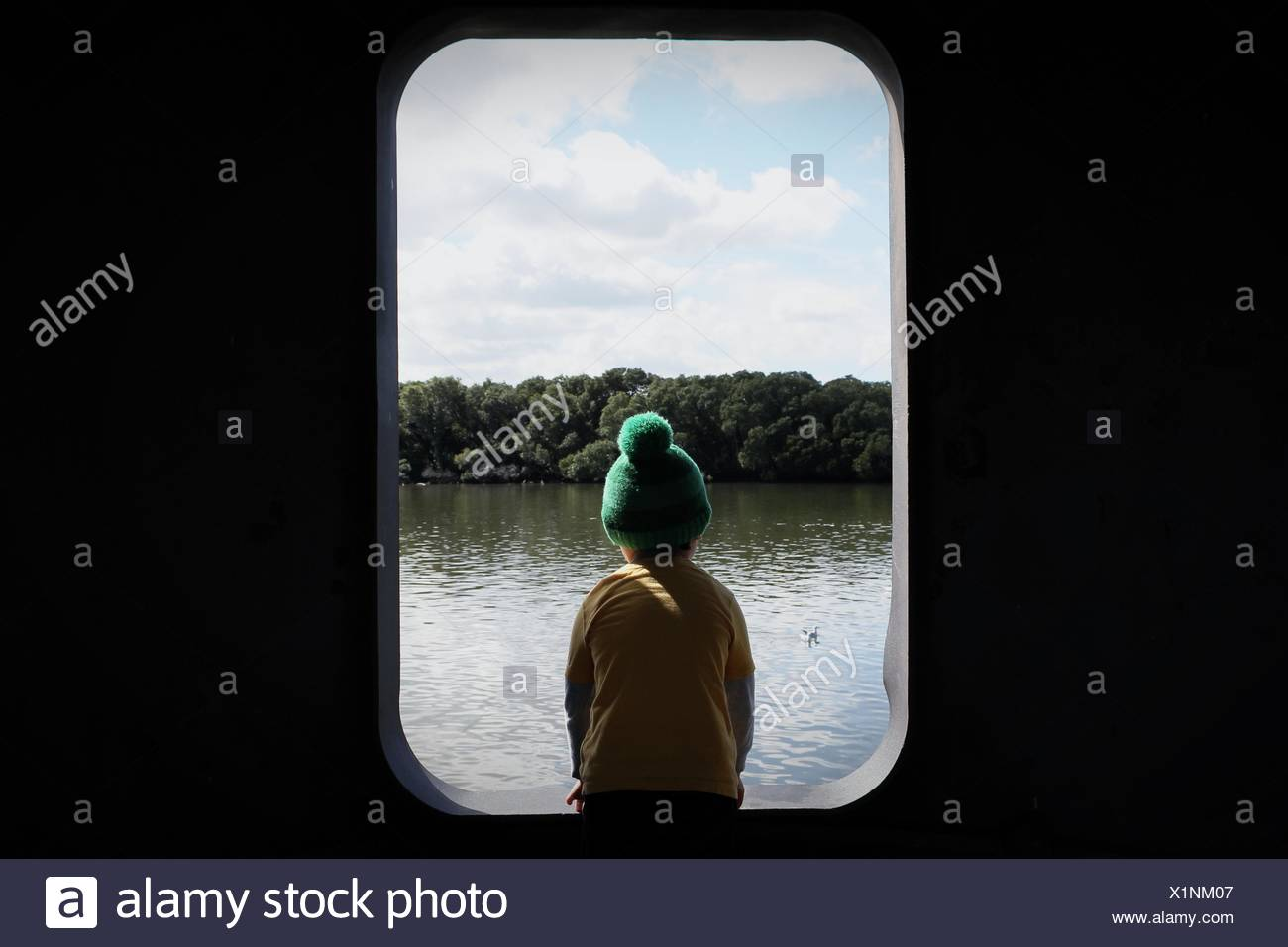 Rear View Of Boy Wearing Knit Hat Sitting In Front Of River - Stock Image