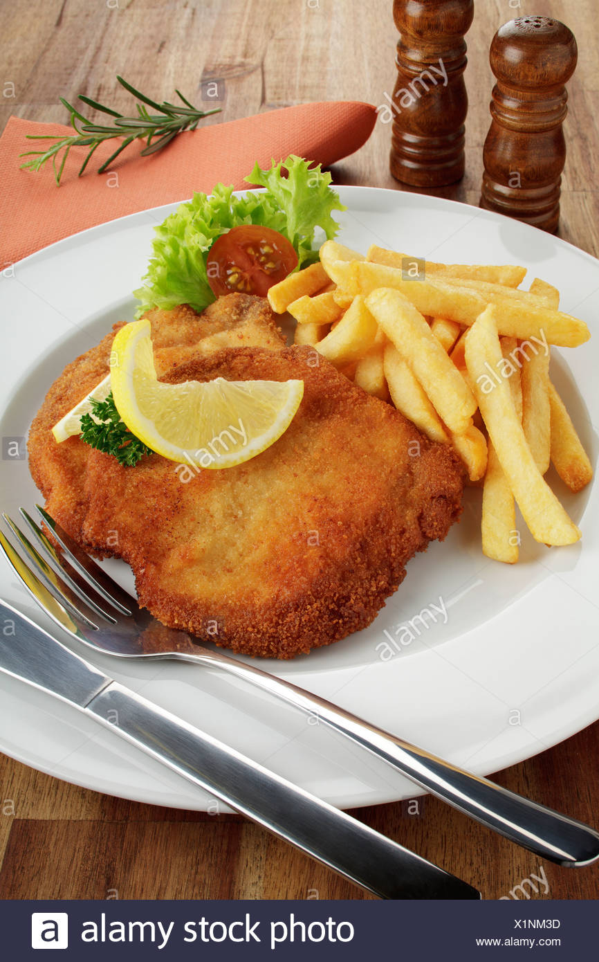 Breaded pork escalope Viennese style with lemon slice and French fries - Stock Image