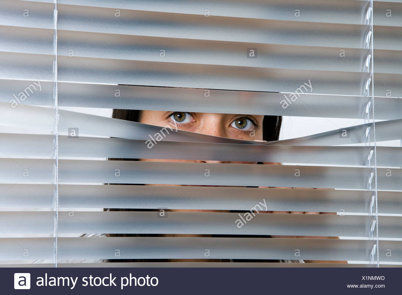 A young woman peering through Venetian blinds - Stock Image