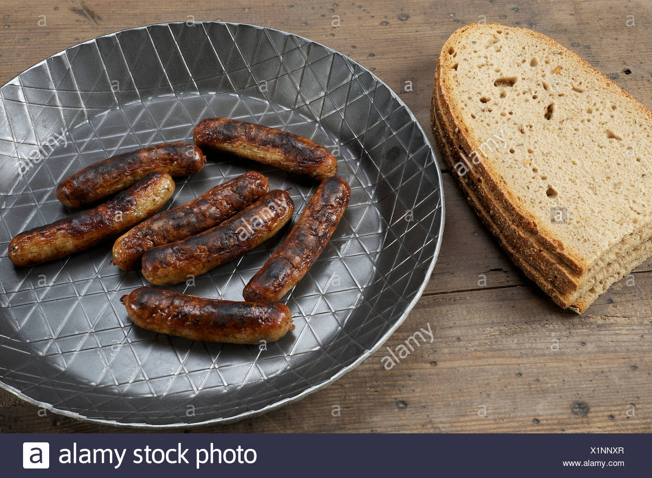 Nuernberger bratwurst in an iron pan with bread - Stock Image