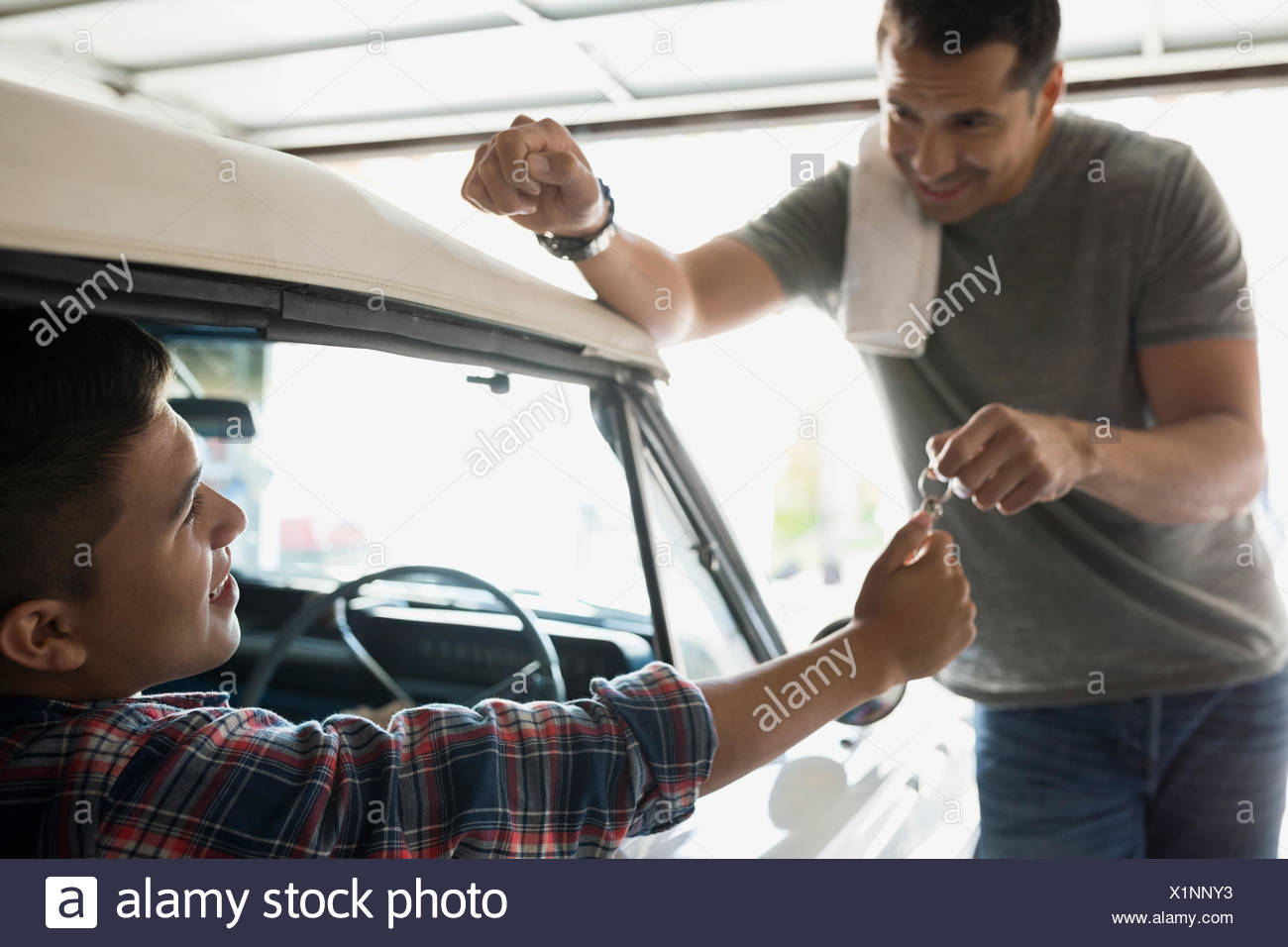 Father giving son keys to vintage car in garage - Stock Image