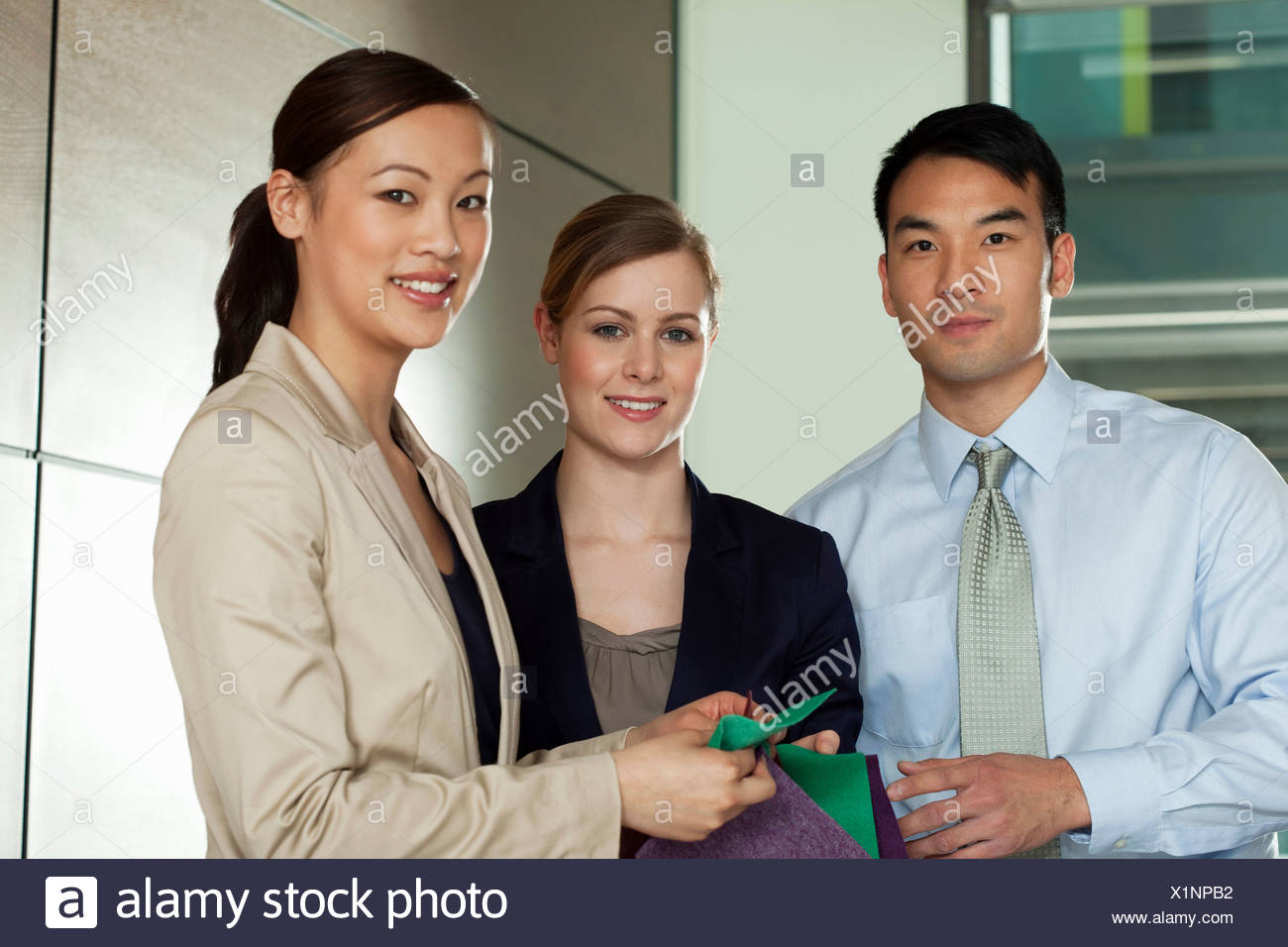 Multi racial businesspeople with colour swatches, portrait - Stock Image