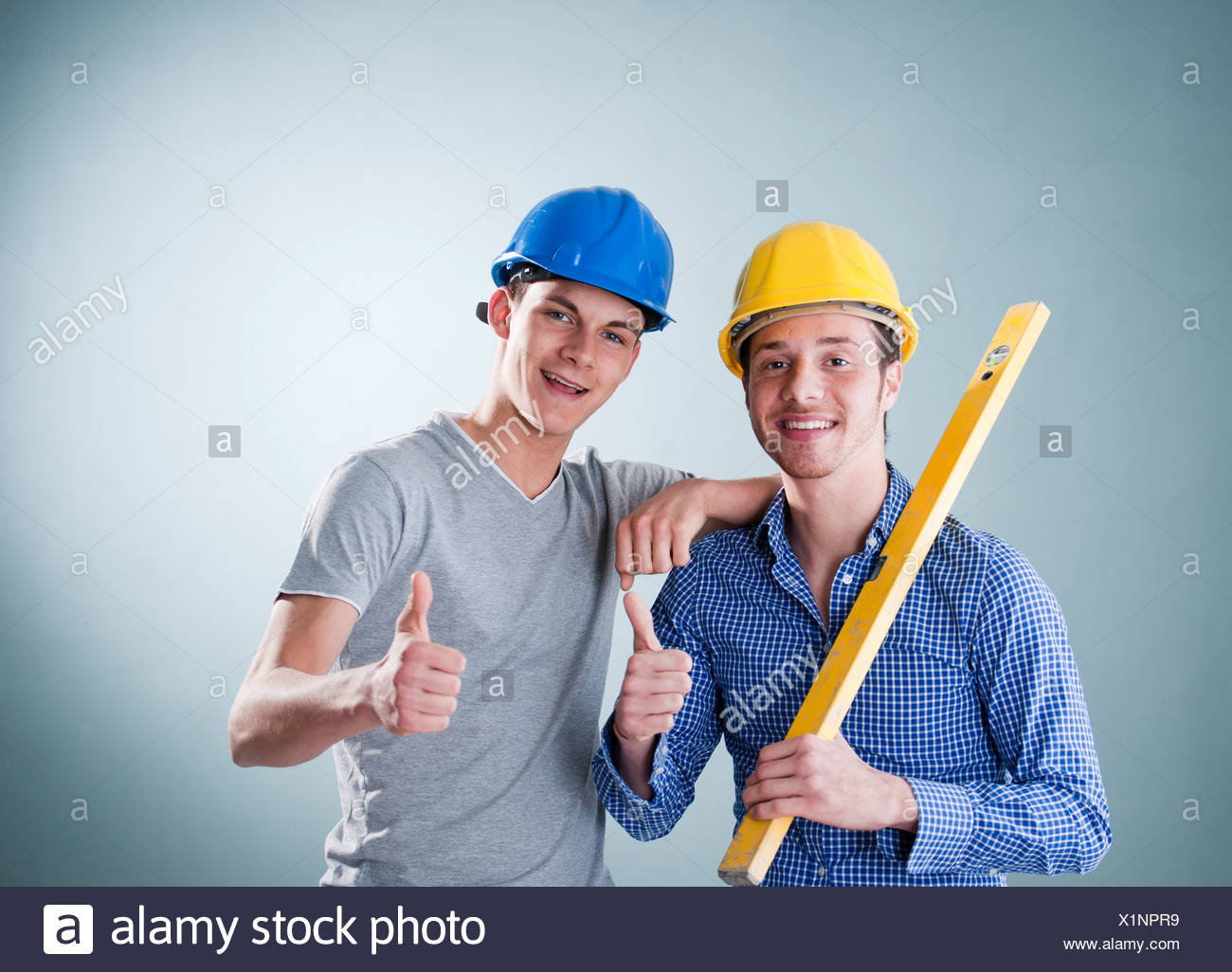 Two young tradesmen holding a spirit level - Stock Image