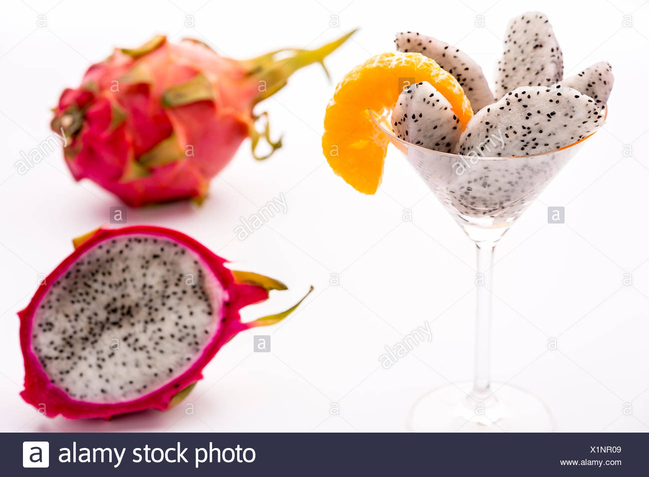The juicy pulp of the Pitahaya blanca presented in a glass and decorated with a mandarine slice. This exotic fruit is also called strawberry pear, nanettika fruit or pitaya. - Stock Image