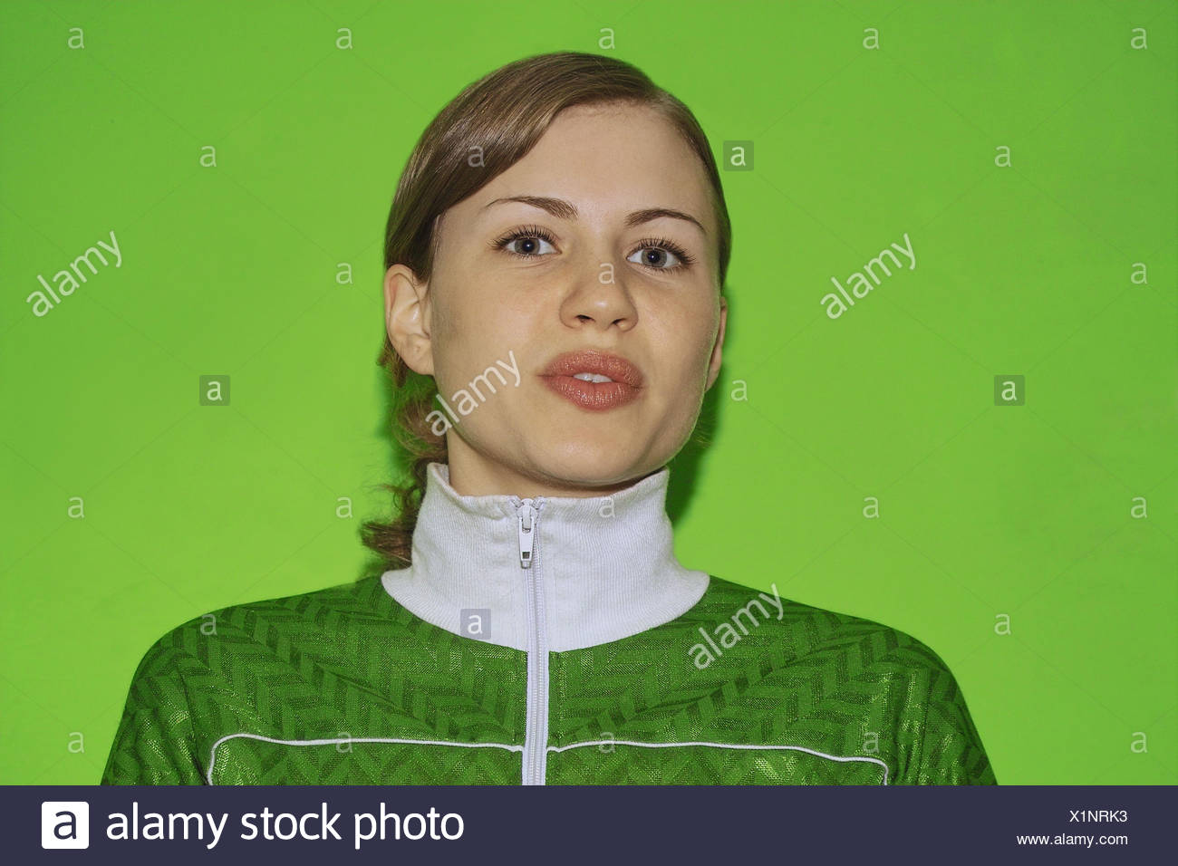 Woman, young, horse's tail, portrait, women's portrait, 20-30 years, long-haired, wavy, jacket, tracksuit top, sportily, collars, sportive, facial play, background green - Stock Image