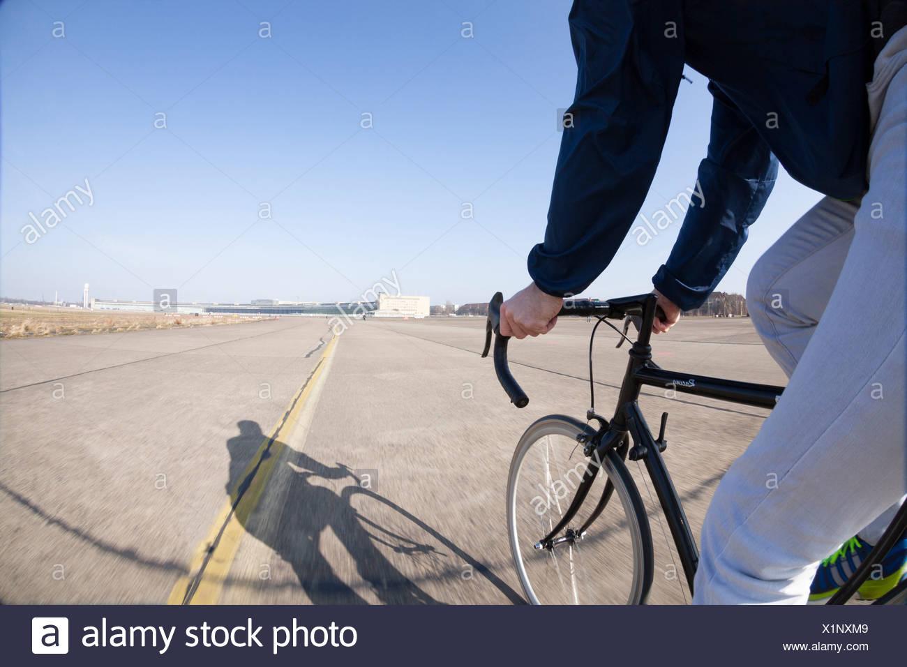 Germany, Berlin, racing biker driving at Tempelhofer Feld formerly Berlin Tempelhof Airport, partial view - Stock Image