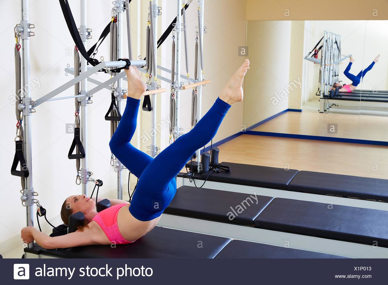 Pilates reformer woman tower exercise workout at gym indoor. - Stock Image